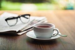 Φλυτζάνι καφέ γυαλιών ανάγνωσης εφημερίδων Στοκ Εικόνες