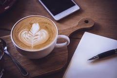 Φλυτζάνι καφέ και νόστιμο κέικ στον ξύλινο πίνακα και την κενή αναμονή εγγράφου Στοκ φωτογραφία με δικαίωμα ελεύθερης χρήσης