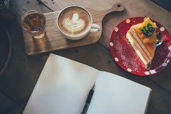 Φλυτζάνι καφέ και νόστιμο κέικ στον ξύλινο πίνακα και την κενή αναμονή εγγράφου Στοκ Φωτογραφίες