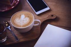 Φλυτζάνι καφέ και νόστιμο κέικ στον ξύλινο πίνακα και την κενή αναμονή εγγράφου Στοκ εικόνες με δικαίωμα ελεύθερης χρήσης