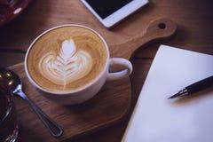 Φλυτζάνι καφέ και νόστιμο κέικ στον ξύλινο πίνακα και την κενή αναμονή εγγράφου Στοκ Εικόνες