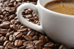 Φλυτζάνι καφέ και στενός επάνω υποβάθρου φασολιών καφέ Στοκ Φωτογραφίες