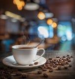 Φλυτζάνι καφέ και φασόλια καφέ στον ξύλινο πίνακα Στοκ φωτογραφία με δικαίωμα ελεύθερης χρήσης
