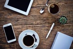Φλυτζάνι καφέ καυτό και γραφείο μανδρών σημειωματάριων lap-top στοκ φωτογραφία με δικαίωμα ελεύθερης χρήσης