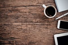 Φλυτζάνι καφέ καυτό και γραφείο μανδρών σημειωματάριων lap-top στοκ φωτογραφίες