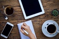 Φλυτζάνι καφέ καυτό και γραφείο μανδρών σημειωματάριων lap-top στοκ φωτογραφία