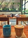 Φλυτζάνι καφέ καυτό στον πίνακα και την καρέκλα καφέδων στοκ εικόνα