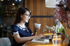 Φλυτζάνι καφέ λαβής γυναικών και εργασία στο lap-top, επιχειρησιακή έννοια στοκ φωτογραφία με δικαίωμα ελεύθερης χρήσης