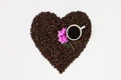 Φλυτζάνι καφέ, λουλούδια και φασόλια καφέ σε μια μορφή μιας καρδιάς isolat στοκ εικόνα