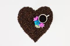 Φλυτζάνι καφέ, λουλούδια και φασόλια καφέ σε μια μορφή μιας καρδιάς isolat στοκ εικόνα με δικαίωμα ελεύθερης χρήσης