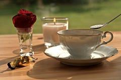 Φλυτζάνι καφέ με ένα κουτάλι της ζάχαρης και ένα ροδαλό άνθος μπροστά από ένα καίγοντας κερί Στοκ Φωτογραφία