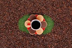 Φλυτζάνι καφέ με τα μπισκότα στη χλόη με μια δέσμη των φασολιών καφέ γύρω στοκ φωτογραφία