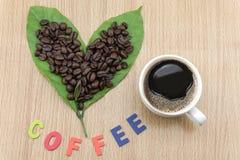 Φλυτζάνι καφέ με τα φασόλια καφέ και τα φύλλα καφέ Στοκ Εικόνα