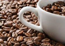 Φλυτζάνι καφέ με τη μακροεντολή υποβάθρου φασολιών καφέ Στοκ φωτογραφία με δικαίωμα ελεύθερης χρήσης