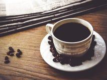 Φλυτζάνι καφέ με το έγγραφο φασολιών καφέ και ειδήσεων Στοκ φωτογραφία με δικαίωμα ελεύθερης χρήσης