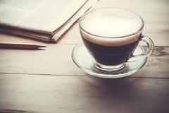 Φλυτζάνι καφέ με το newpaper στον ξύλινο πίνακα το πρωί στοκ φωτογραφίες με δικαίωμα ελεύθερης χρήσης