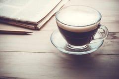 Φλυτζάνι καφέ με το newpaper στον ξύλινο πίνακα το πρωί στοκ φωτογραφία με δικαίωμα ελεύθερης χρήσης
