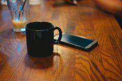 φλυτζάνι καφέ που τίθεται εκτός από το κινητό τηλέφωνο όλη αυτή η τοποθέτηση στο woode Στοκ φωτογραφία με δικαίωμα ελεύθερης χρήσης