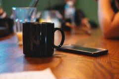 φλυτζάνι καφέ που τίθεται εκτός από το κινητό τηλέφωνο όλη αυτή η τοποθέτηση στο woode Στοκ Εικόνες