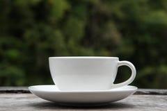 Φλυτζάνι καφέ στο ξύλινο επιτραπέζιο θολωμένο φύση υπόβαθρο στοκ φωτογραφία