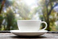 Φλυτζάνι καφέ στο ξύλινο επιτραπέζιο θολωμένο φύση υπόβαθρο στοκ φωτογραφίες