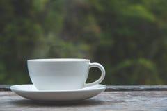 Φλυτζάνι καφέ στο ξύλινο επιτραπέζιο θολωμένο φύση υπόβαθρο στοκ εικόνες