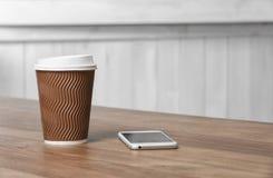 Φλυτζάνι καφέ χαρτονιού με το καπάκι και τηλέφωνο στον ξύλινο πίνακα στοκ εικόνες με δικαίωμα ελεύθερης χρήσης