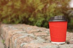 Φλυτζάνι καφέ χαρτονιού με το καπάκι στην επιφάνεια πετρών υπαίθρια στοκ εικόνα