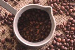 Φλυτζάνι με τα φυσικά καφετιά ψημένα φασόλια καφέ στοκ φωτογραφία με δικαίωμα ελεύθερης χρήσης
