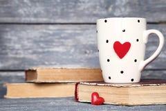 Φλυτζάνι με τις κόκκινα καρδιές και τα βιβλία στοκ εικόνα