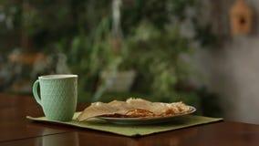 Φλυτζάνι με τον ατμό στον πίνακα και τις τηγανίτες η πρασινάδα στο υπόβαθρο όμορφο σπίτι κουζινών απόθεμα βίντεο