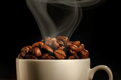 Φλυτζάνι που γεμίζουν με τα φασόλια καφέ στοκ εικόνες
