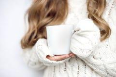 Φλυτζάνι στα χέρια ενός κοριτσιού σε ένα πουλόβερ σε ένα άσπρο υπόβαθρο στοκ εικόνες