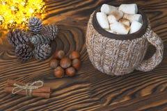 Φλυτζάνι της καυτής σοκολάτας με marshmallows, τα καρύδια και την κανέλα σε μια εκλεκτής ποιότητας ξύλινη επιφάνεια με τα φω'τα Χ στοκ εικόνα
