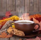 Φλυτζάνι του βρασίματος στον ατμό του καφέ και του μπισκότου σε ένα αγροτικό ξύλινο υπόβαθρο στοκ εικόνες