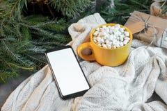 Φλυτζάνι του κακάου με Marshmallows και του κινητού τηλεφώνου με την κενή οθόνη στο υπόβαθρο χριστουγεννιάτικων δέντρων και πουλό στοκ φωτογραφίες με δικαίωμα ελεύθερης χρήσης