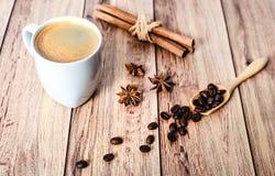 Φλυτζάνι του καυτού καφέ, των ραβδιών κανέλας και των φασολιών καφέ που ανατρέπουν έξω από μια ξύλινη σέσουλα στον ξύλινο αγροτικ στοκ εικόνες με δικαίωμα ελεύθερης χρήσης