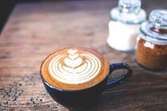 Φλυτζάνι του καυτού καφέ latte στον ξύλινο πίνακα Στοκ Φωτογραφίες