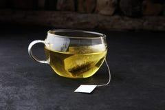 Φλυτζάνι του καυτού τσαγιού με teabag Το φλυτζάνι είναι από το σαφές γυαλί στοκ φωτογραφίες