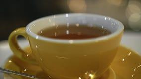 Φλυτζάνι του καυτού τσαγιού στον καφέ φιλμ μικρού μήκους