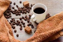 Φλυτζάνι του μαύρου καφέ, ψημένα φασόλια καφέ με τα κομμάτια της ζάχαρης καλάμων στον ξύλινο πίνακα Τοπ όψη Στοκ Φωτογραφίες