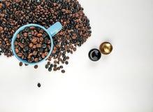 Φλυτζάνι του μπλε καφέ, με τα φασόλια καφέ που περιβάλλουν, και δύο κάψες καφέ, με το κενό διάστημα r στοκ φωτογραφία