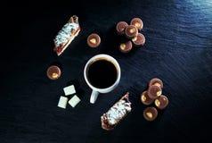 Φλυτζάνι του πρόσφατα παρασκευασμένου καφέ, καραμέλες σοκολάτας γάλακτος και κομμάτια του κέικ Στοκ Εικόνες
