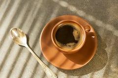 Φλυτζάνι του πρόσφατα παρασκευασμένου καφέ πρωινού, δίπλα στο κουταλάκι του γλυκού, στον πίνακα Στοκ Εικόνα