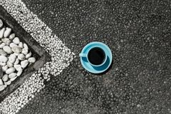 Φλυτζάνι του σκοτεινού καφέ στο σκοτεινός-γκρίζο υπερυψωμένο μονοπάτι με το άσπρο σχεδιάγραμμα στοκ εικόνες