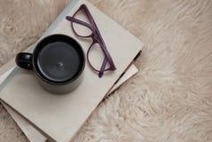Φλυτζάνι του τσαγιού ή του καφέ με τα βιβλία και γυαλιά στο μαλακό τάπητα γουνών Χειμερινή διάθεση στοκ εικόνα με δικαίωμα ελεύθερης χρήσης