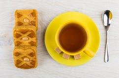 Φλυτζάνι του τσαγιού, ζάχαρη στο πιατάκι, μπισκότα με το αμυγδαλωτό, κουταλάκι του γλυκού Στοκ Φωτογραφία