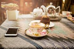 Φλυτζάνι του τσαγιού και φέτα του δοχείου σοκολάτας και τσαγιού με το φως του ήλιου Στοκ Εικόνα