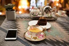 Φλυτζάνι του τσαγιού και φέτα του δοχείου σοκολάτας και τσαγιού με το φως bokeh Στοκ Εικόνες