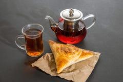 Φλυτζάνι του τσαγιού με την πίτα και teapot γυαλιού στο μαύρο υπόβαθρο Στοκ φωτογραφία με δικαίωμα ελεύθερης χρήσης